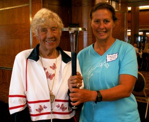 Greta Anderson, swimming legend, holding the World Harmony Run Torch