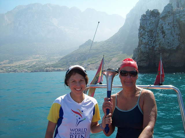 We made it! Holding the World Harmony Run torch at the end of our Gibraltar Straits Swim 2012